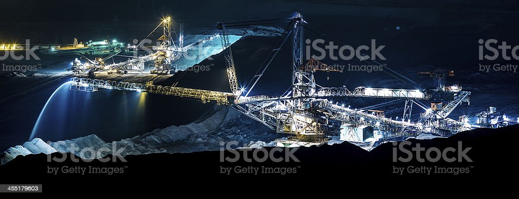 machine in an open coal mine at night stock photo