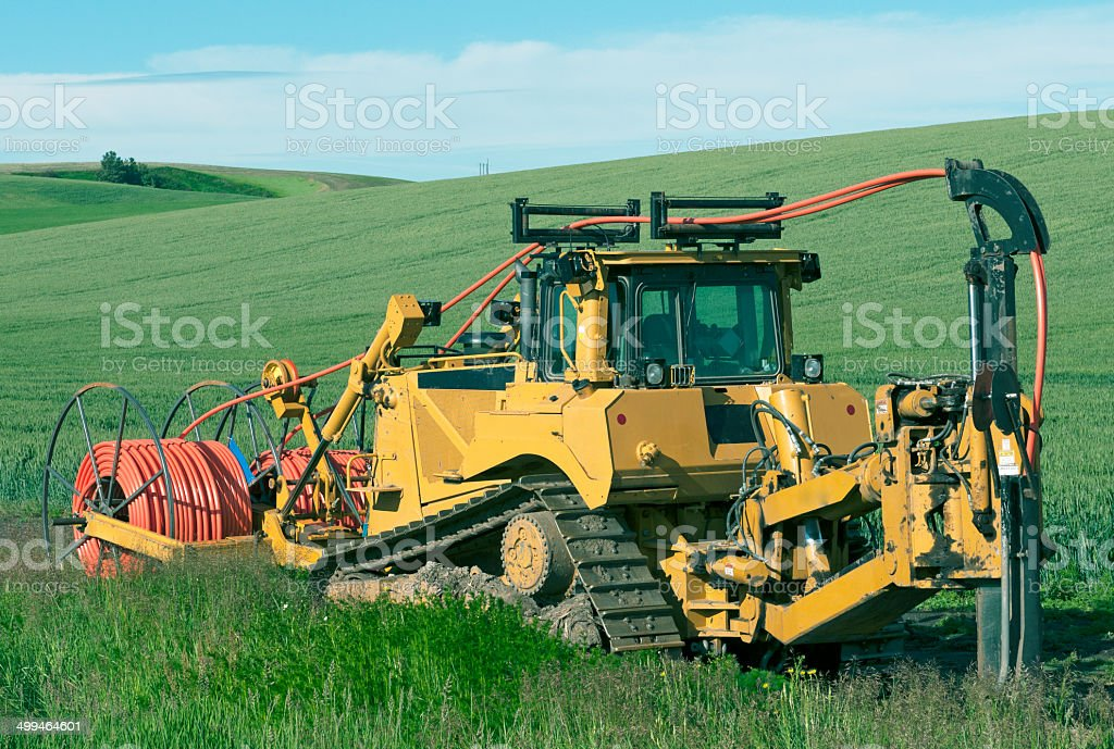 Machine laying cable through wheat field in Washington state stock photo