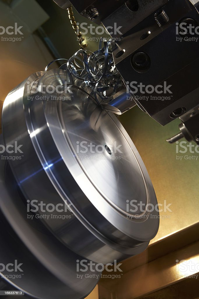 CNC machine making circular grooves and steel filings stock photo