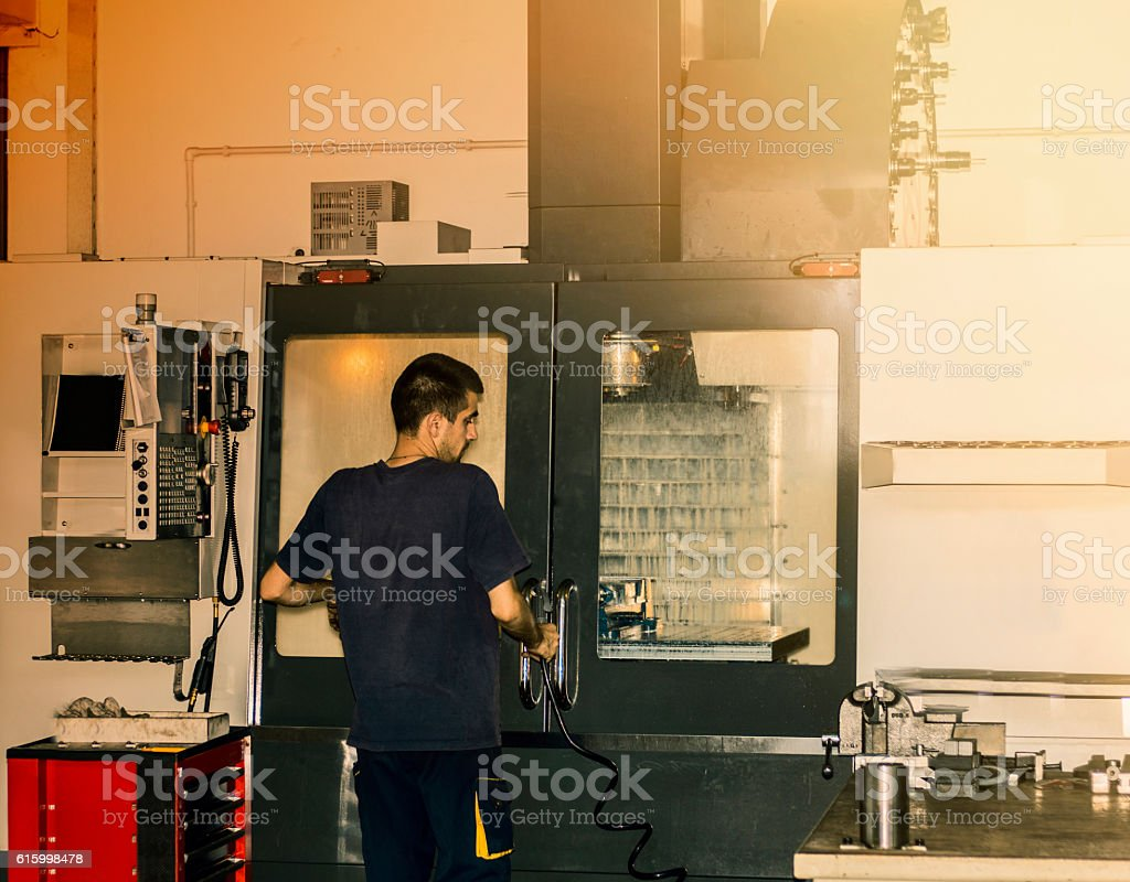 CNC machine operator at tool workshop. stock photo