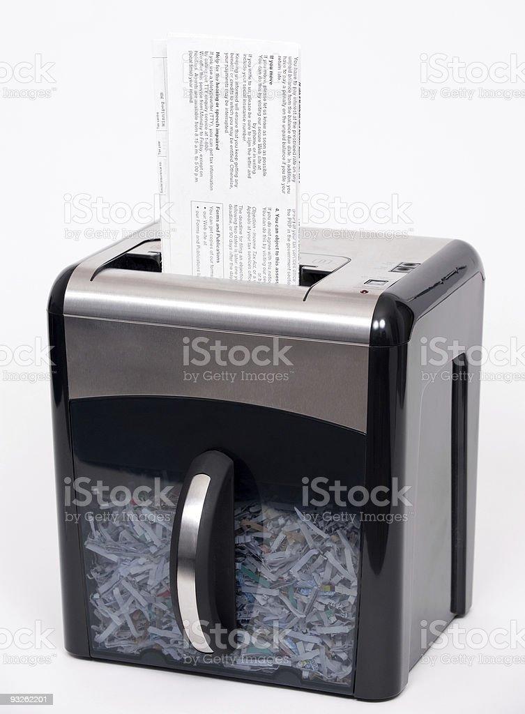 A machine shredding paper into tiny pieces stock photo