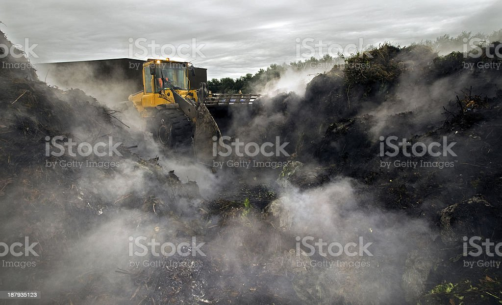 Machine turning compost stock photo