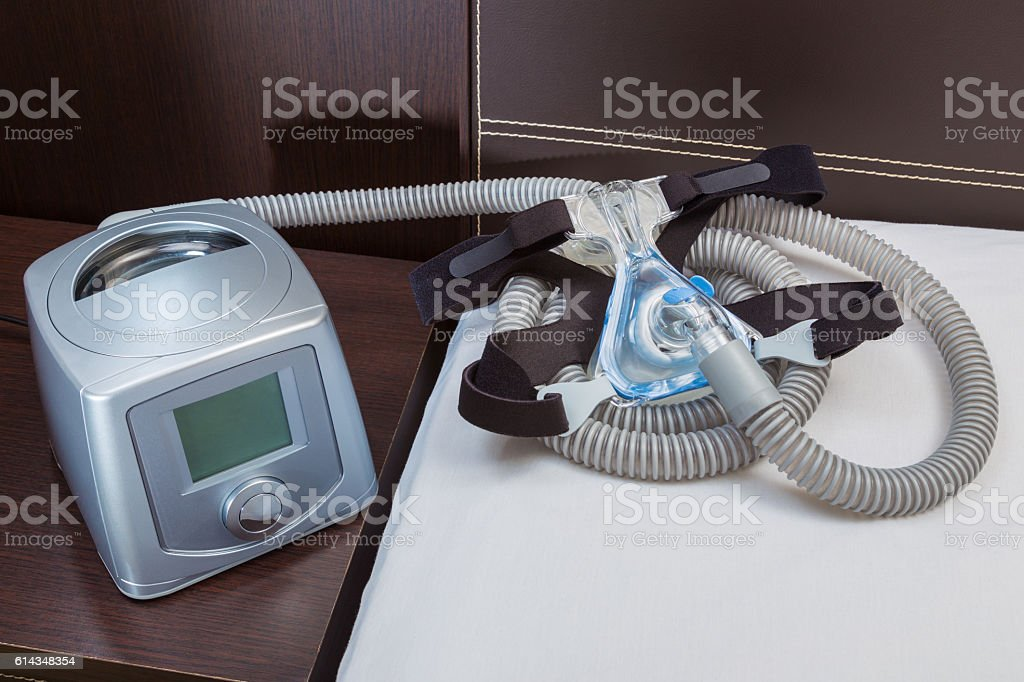 CPAP machine with air hose and head gear mask stock photo