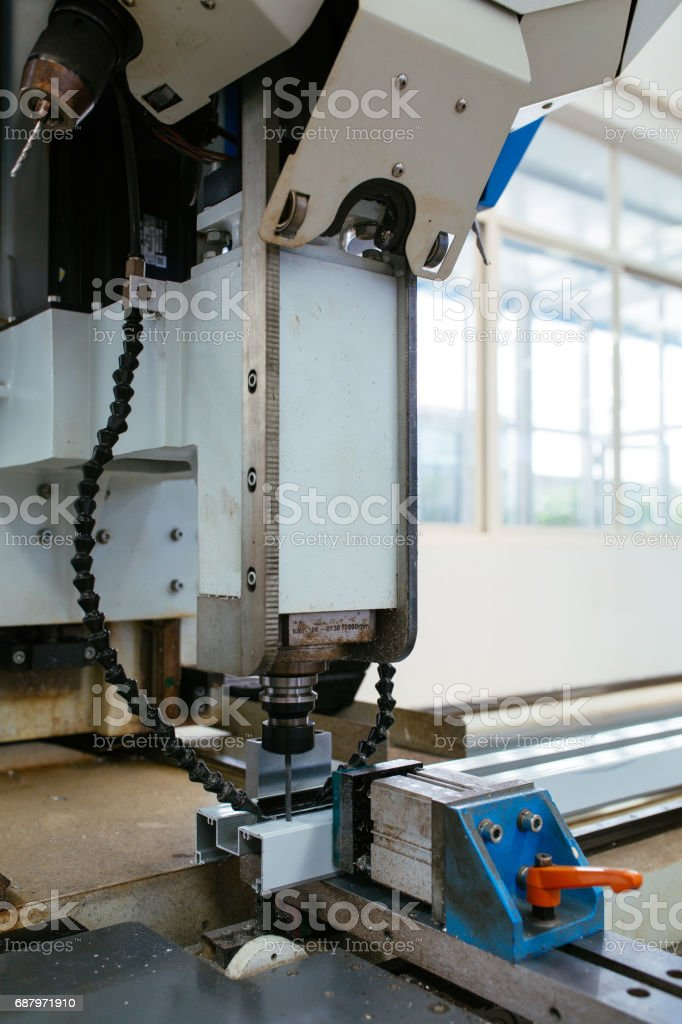 CNC machining center drilling a hole on aluminum profile stock photo