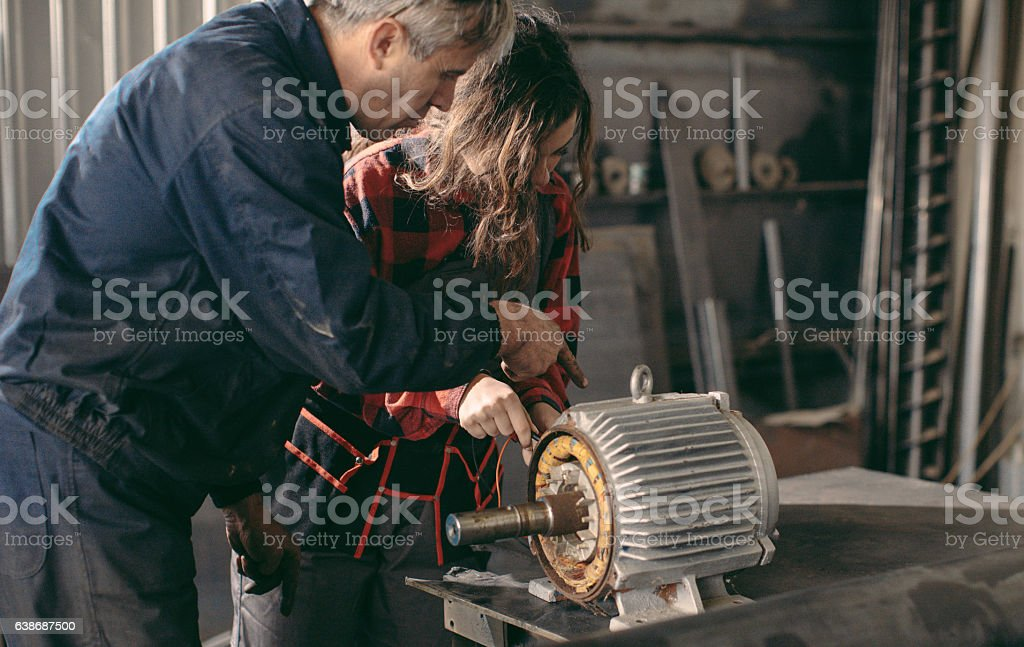 Machinist examining electric motor with voltmeter stock photo