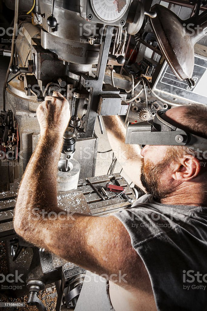 Machinist operating a metal-working milling machine stock photo