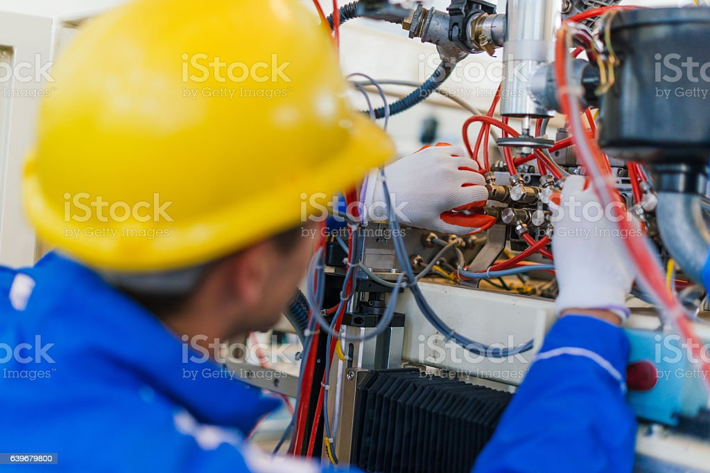 Machinist tightens the leverage on large scale production line machine stock photo