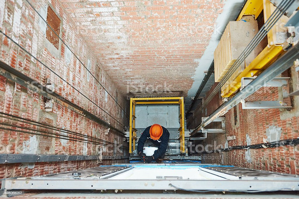 machinists adjusting lift in elevator hoist way stock photo