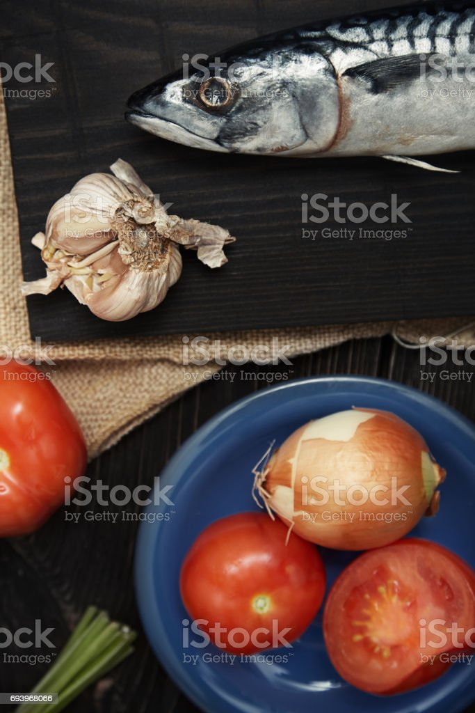 Mackerel and vegetables on a wooden table. Vertical photo stock photo
