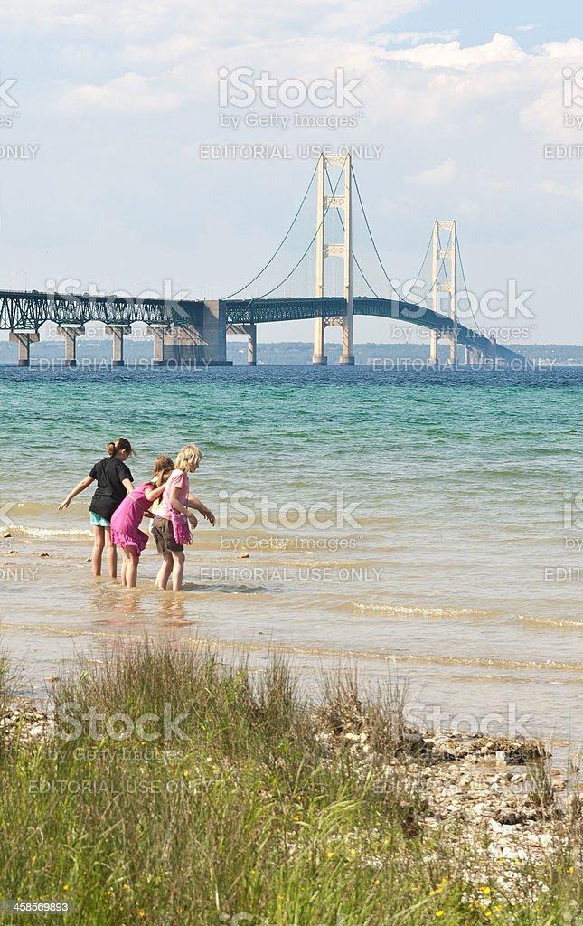 Mackinac Bridge with Children Playing on the Water's Edge stock photo