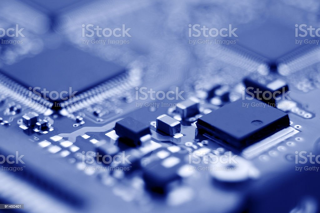 Macro close up of circuit board components with blue tint stock photo