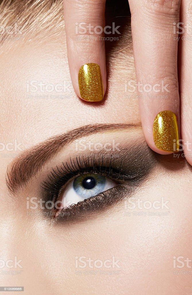 Macro closeup beauty. Smokey makeup gold nails. stock photo