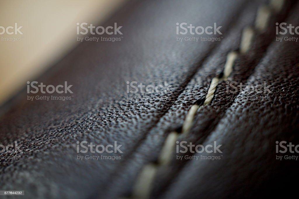 Macro detail of white thread stitching black leather wallet stock photo