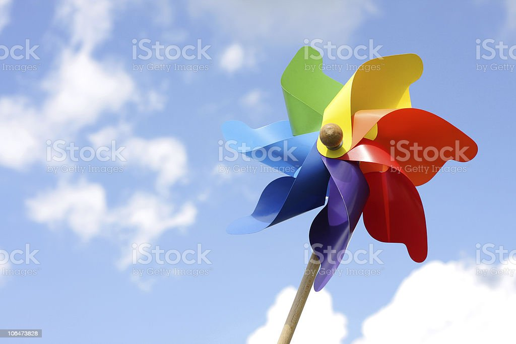 Macro of a colorful pinwheel under a cloudy blue sky stock photo