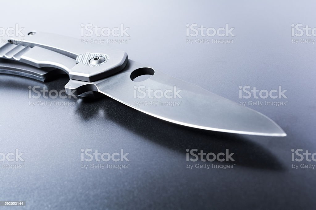 Macro Of An Opened Military Knife On Dark Ground stock photo
