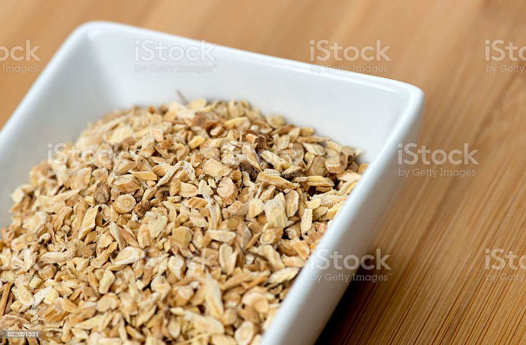 Macro of astragalus root chips against a wooden board stock photo