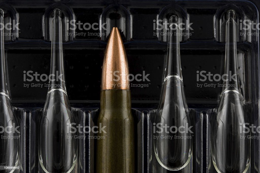 Macro of bullet among ampoules stock photo