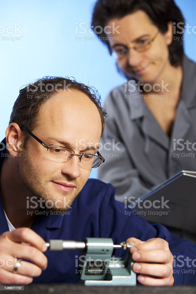 Macro of engineer measuring with assistant stock photo