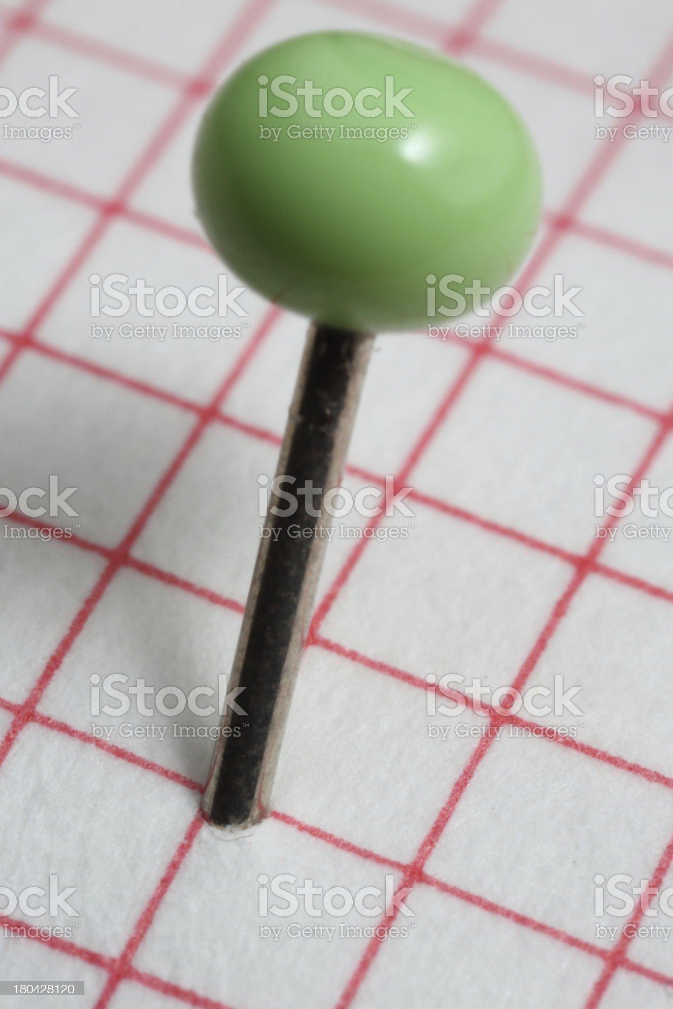 Macro (close-up) of Green Pushpin (thumbtack) isolated on squares royalty-free stock photo