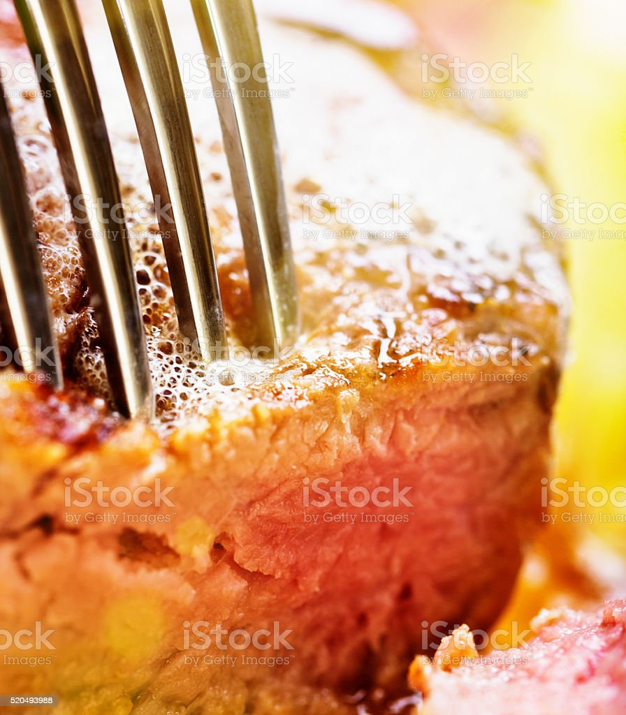 Macro of medium rare fillet steak being pierced by fork stock photo