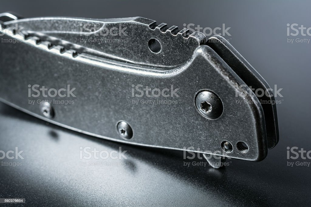 Macro Of Standing Handle Of A Black Closed Folding Knife stock photo