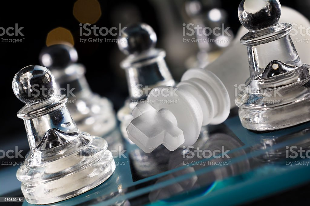 Macro On The Overthrown King On Blue Chessboard stock photo