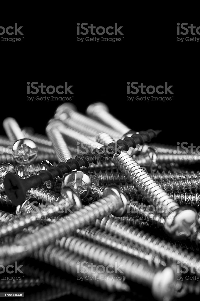 Macro, one black screw in a pile of brass screws royalty-free stock photo