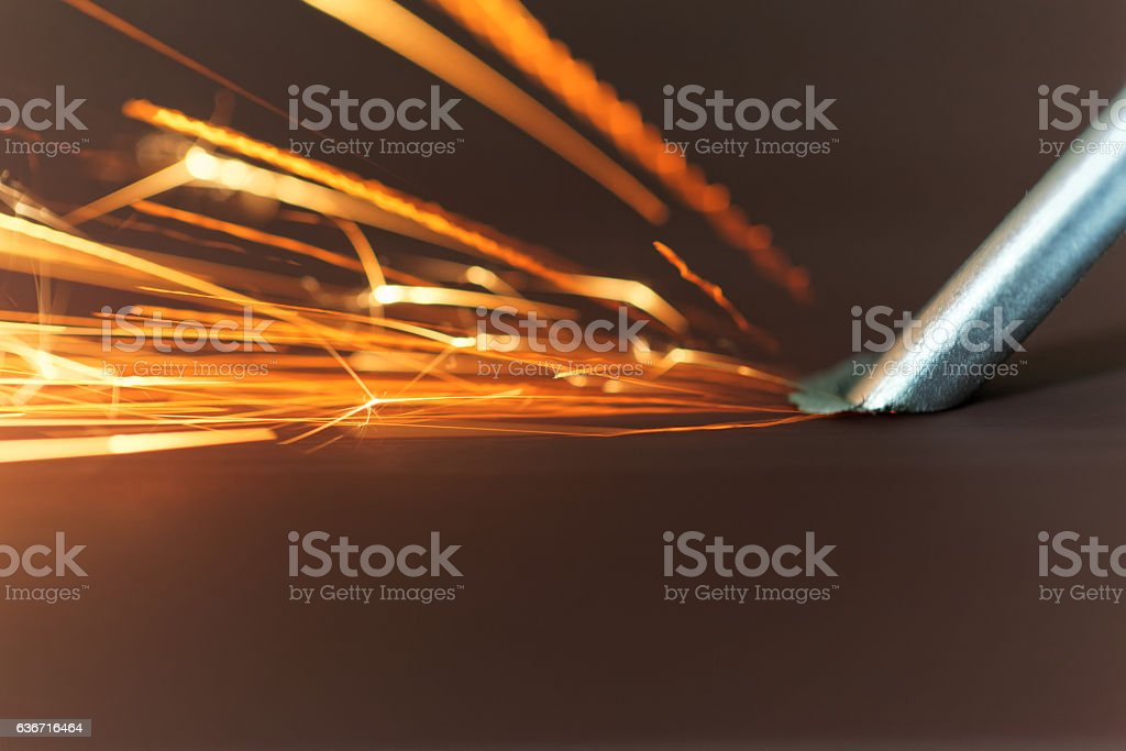 Macro photo of a steel tool on a grinder with sparks. stock photo