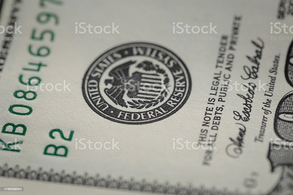 macro photo of federal reserve system symbol on hundred dollar stock photo