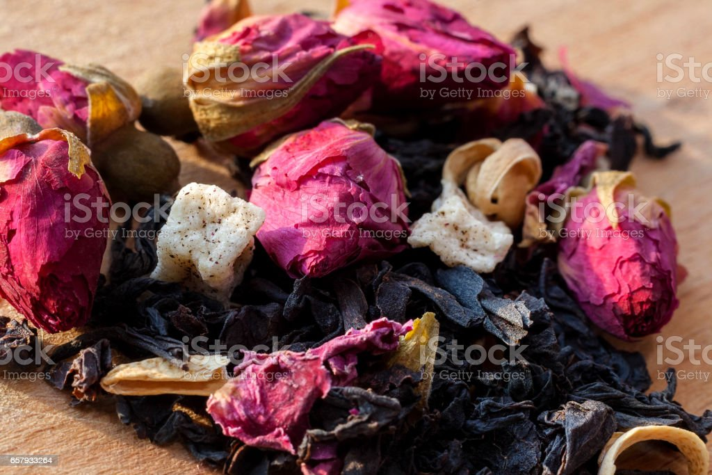 Macro photo of tea with a tea rose. The composition of the heap of tea roses and dried hibiscus flower located on a wooden Board. Black tea with natural rose flower closeup. stock photo
