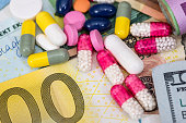 macro pills and tablets on euro and dollar banknotes for