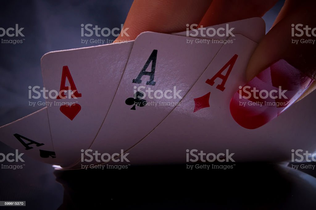 Macro shot of a female hand holding poker of aces stock photo