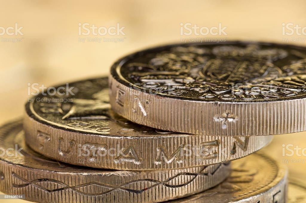 Macro shot of British pound coins precariously balanced. stock photo