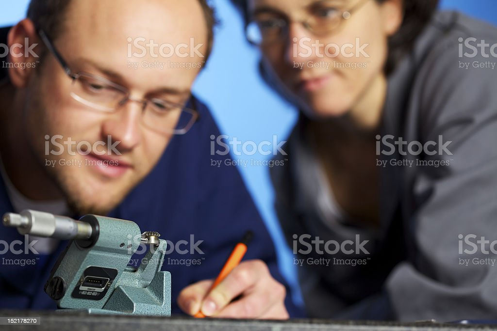 Macro shot of engineer recording measurements with assistant stock photo