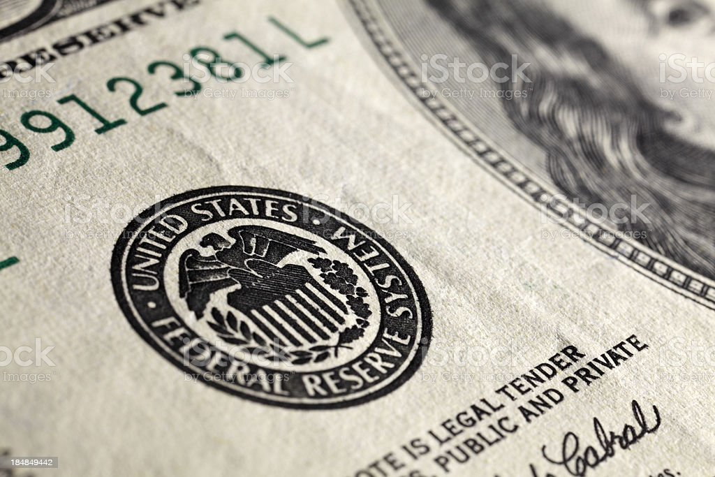 Macro shot of US $100 bill, focus on the seal stock photo