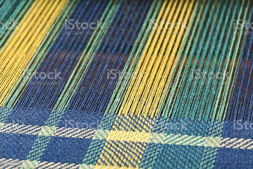 Macro shot of Weaving Plaid Fabric on a Loom. stock photo