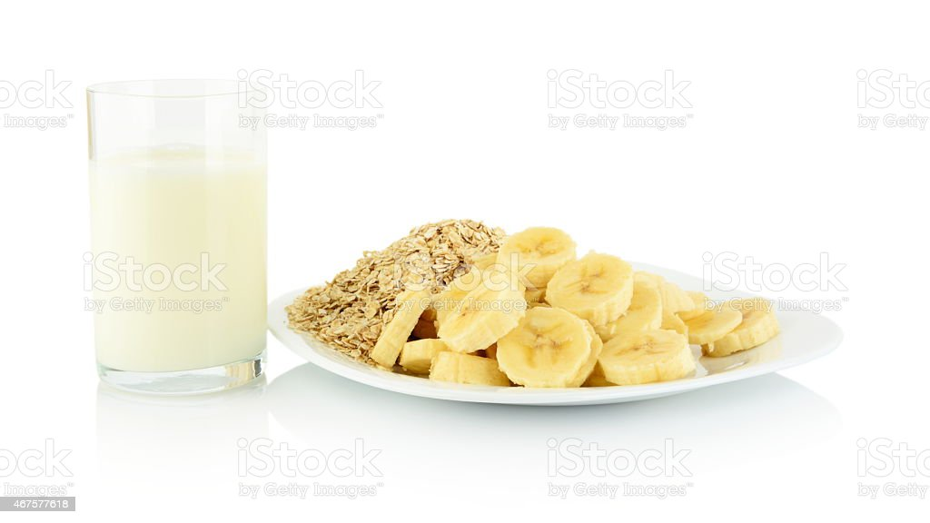 Macro slices banana on plate with glass milk on white stock photo