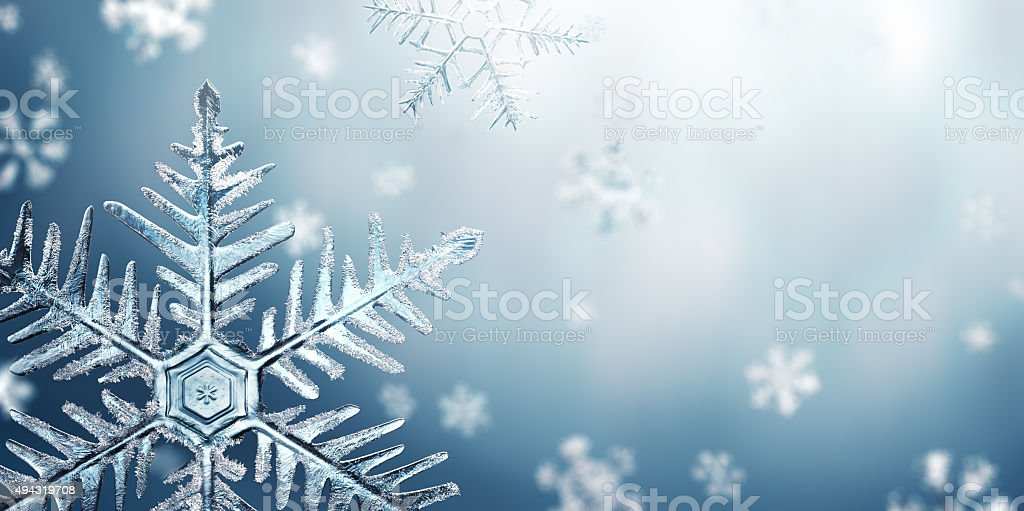 Macro Snowflake and Fallen Defocused Snowflakes stock photo