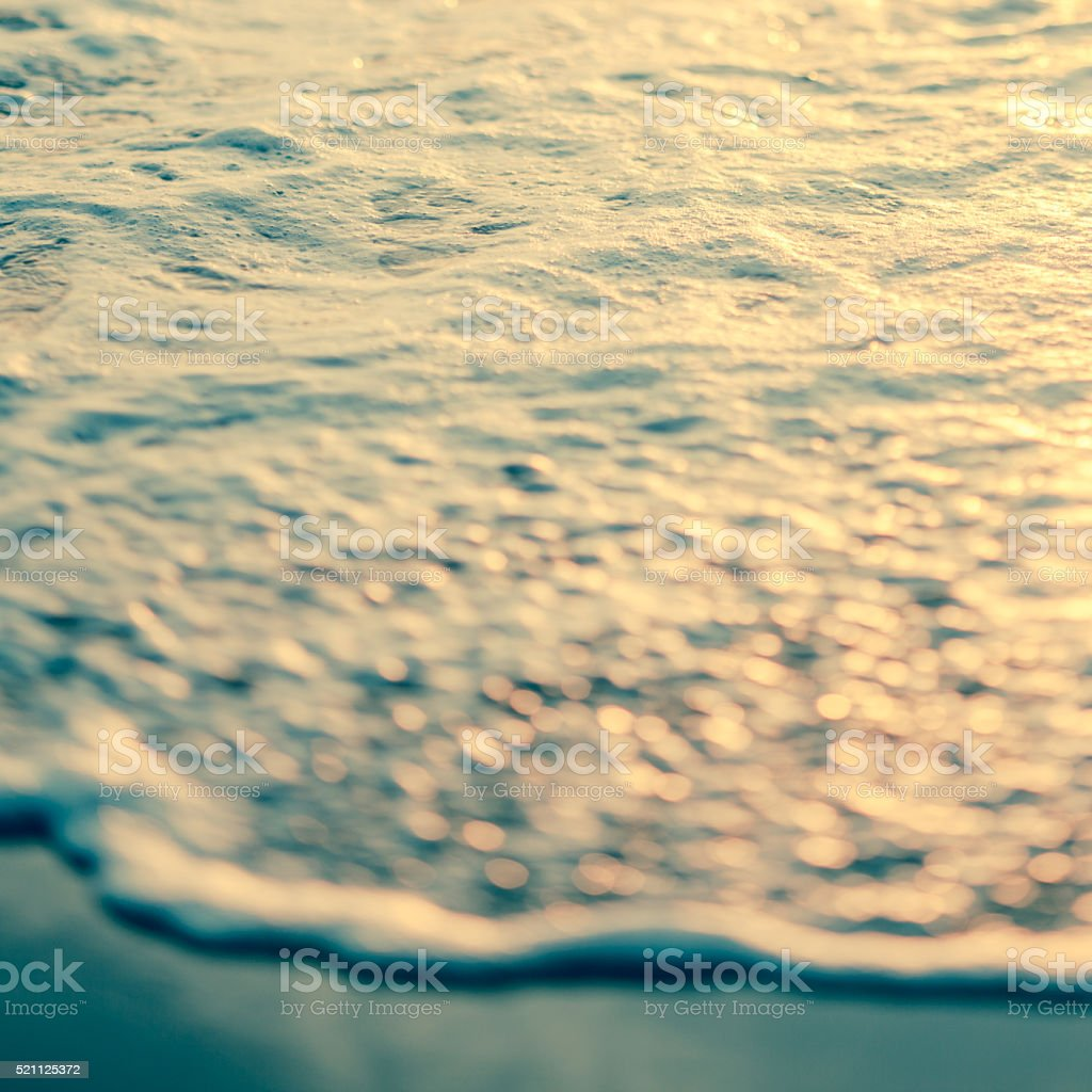 Macro toned and blurred image of ocean wave on beach stock photo