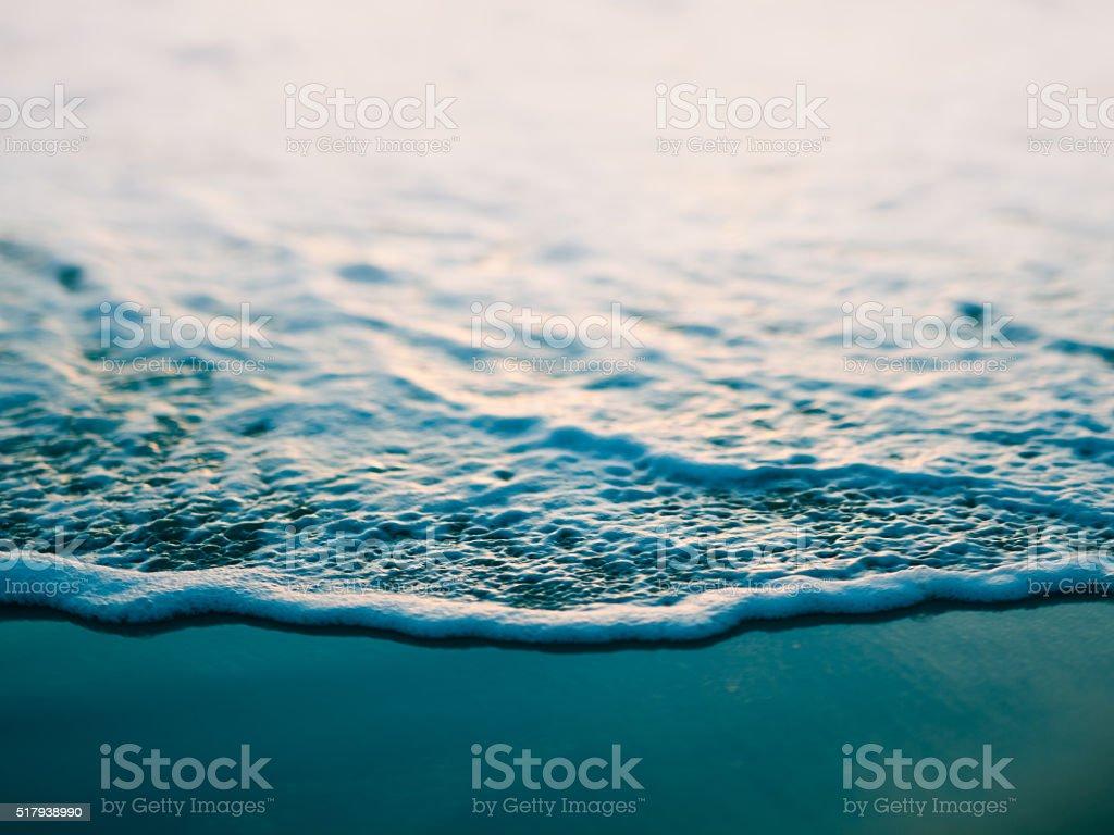 Macro toned image of ocean wave on beach stock photo