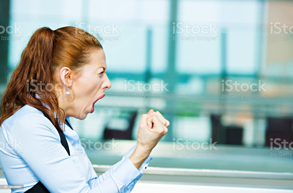 mad angry, upset, hostile young businesswoman, worker, furious yelling hands, fists in air stock photo