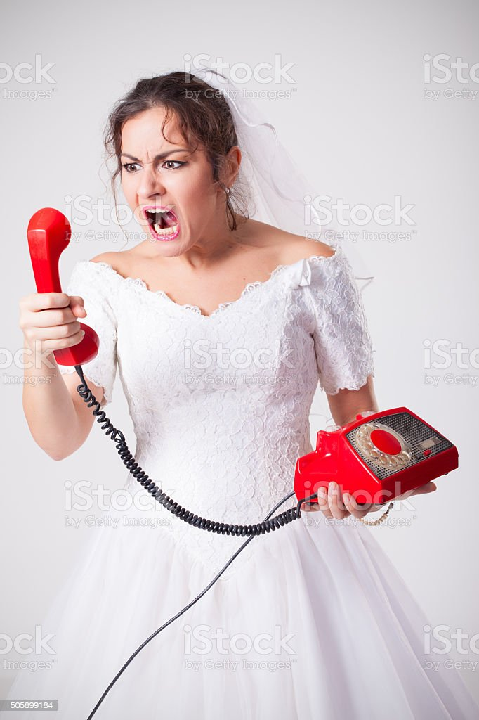 Mad bride screaming on phone stock photo