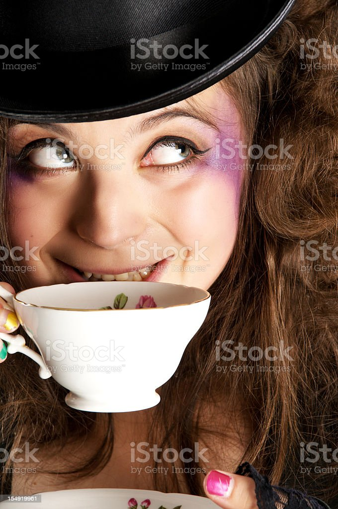 Mad hatter girl smiles about to drink tea. stock photo