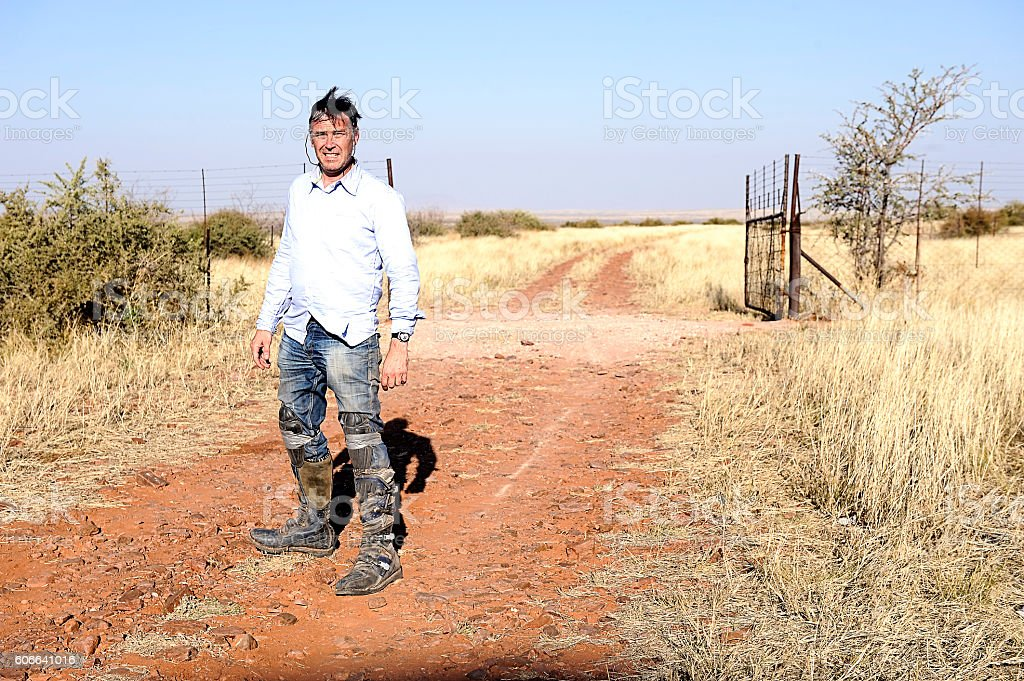 mad man on farm road wearing boots stock photo
