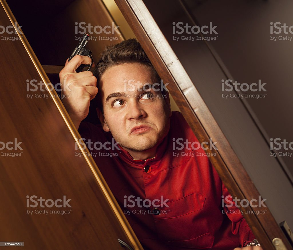 Mad porter with gun hiding in a hotel room stock photo