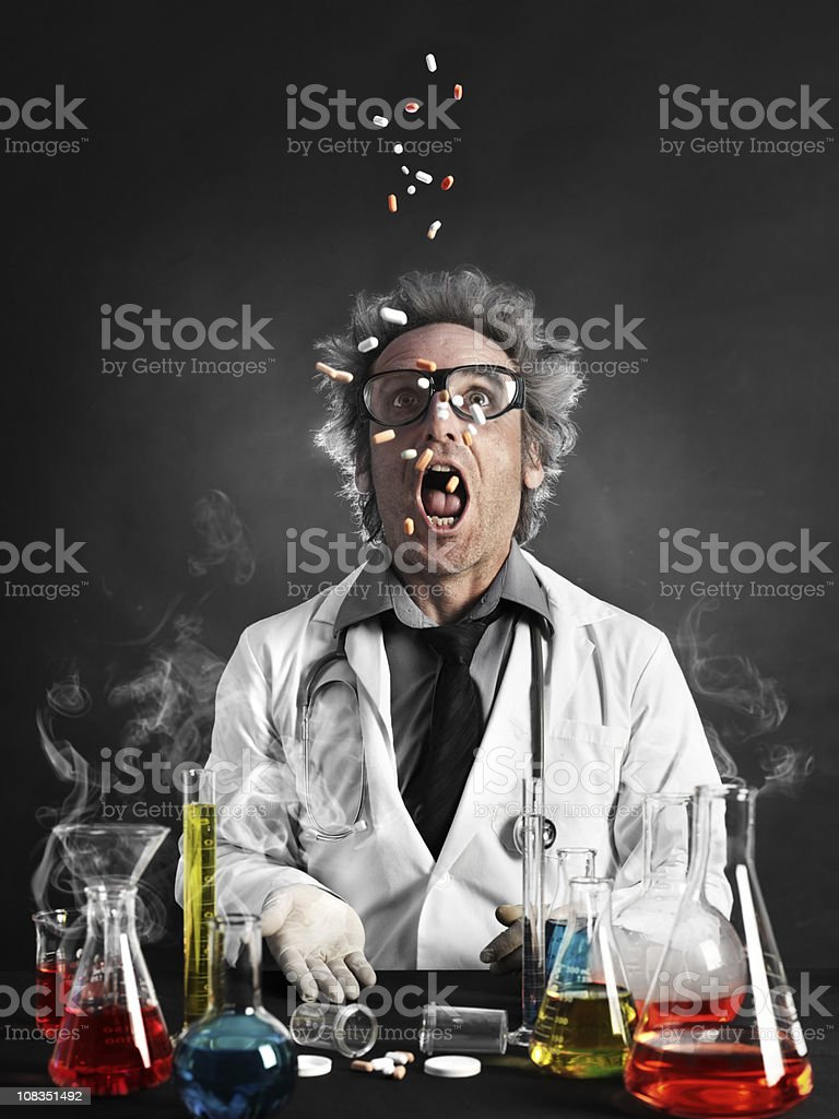 Mad professor eating pills stock photo
