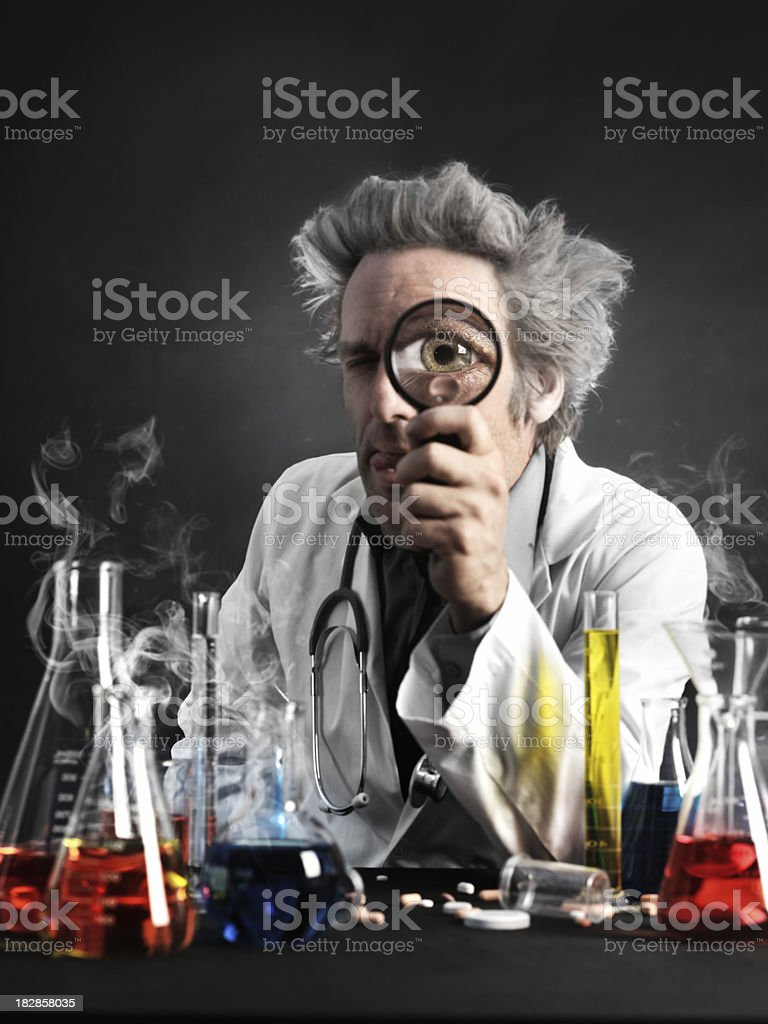 Mad professor looking through magnifyer stock photo