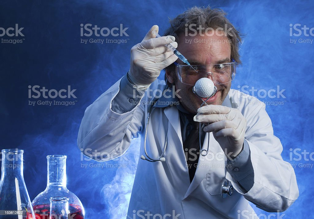 Mad Scientist with a Golf Ball and Hypodermic Needle stock photo