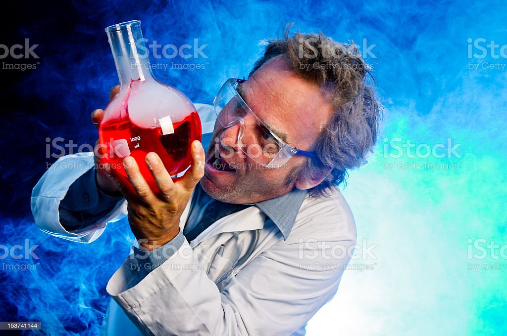 A mad scientist with red potion in his blue lab stock photo