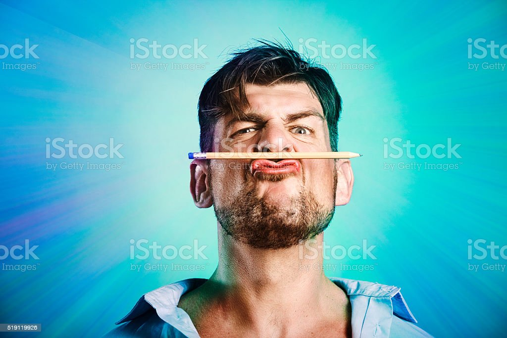 Mad writer holds a pencil with his lips stock photo